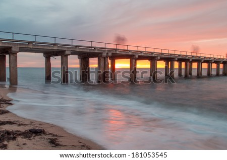 Dromana Pier on the Mornington Peninsula, near Melbourne Australia, at sunset.  The photo is a long second exposure and the figures on the pier appear ghostly. - stock photo