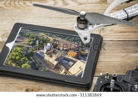 drone aerial photography concept - reviewing aerial picture of grain elevators  on a digital tablet with a drone rotor and radio control transmitter, - stock photo