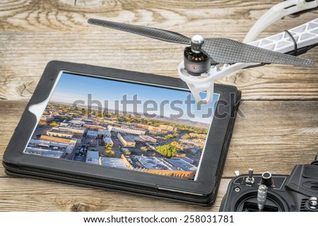 drone aerial photography concept - reviewing aerial pictures of Fort Collins downtown on a digital tablet with a drone rotor and radio control transmitter, - stock photo