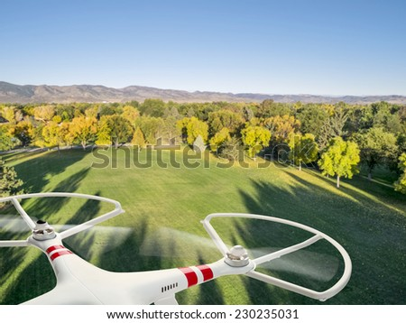 drone flying over a park in fall colors under morning light with deep long shadows - stock photo