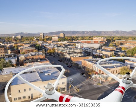 drone flying over city street - privacy invasion or safety issues concept - stock photo