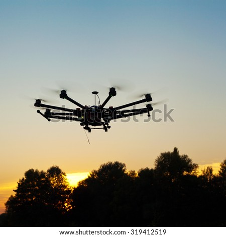 Drone on a background of a beautiful sunset. UAV in flight. Quadrocopters on radio.