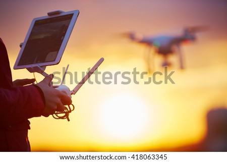 drone quadcopter flying at sunset - stock photo