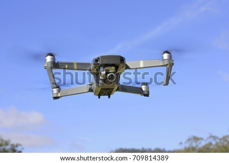Drone quadcopter with digital camera in flight with blue sky