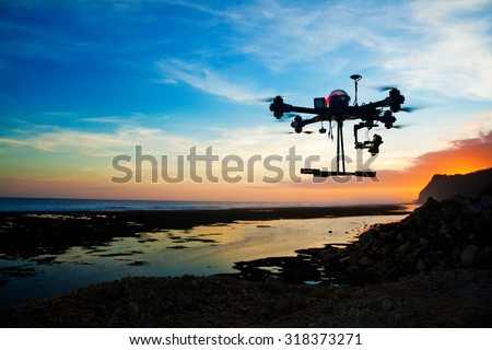 drone silhouette against the sunset sky - stock photo