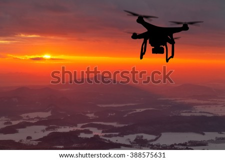 Drone silhouette flying in sunset landscape - stock photo