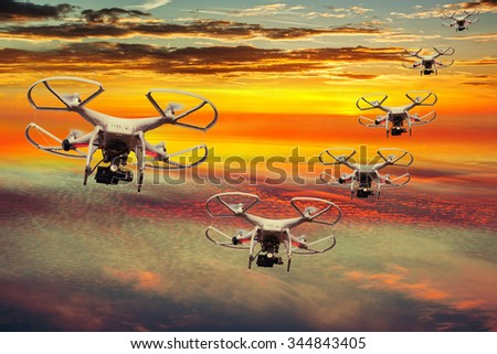 Drones squadron in the sunset with dark clouds. - stock photo