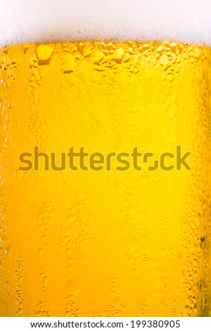 Drop and foam of beer as background - stock photo
