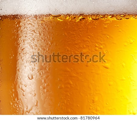 Drop and foam of beer as background. - stock photo