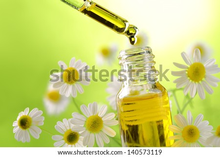 Drop falling from dropper of essential oil, aromatherapy essence, or medicinal liquid - stock photo