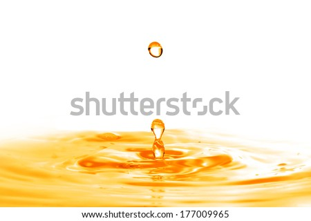 drop falling into orange water with splash isolated on white - stock photo