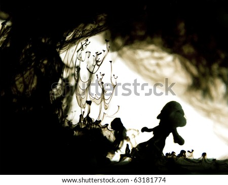 drop of black ink going through water : silhouette of child - stock photo