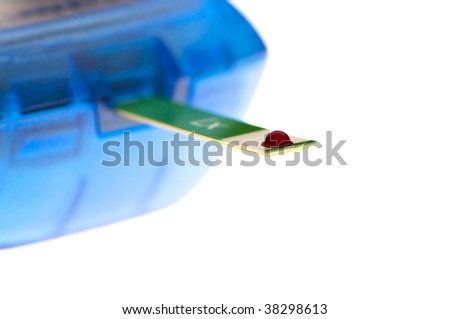 drop of blood on strip being tested for glucose level - stock photo