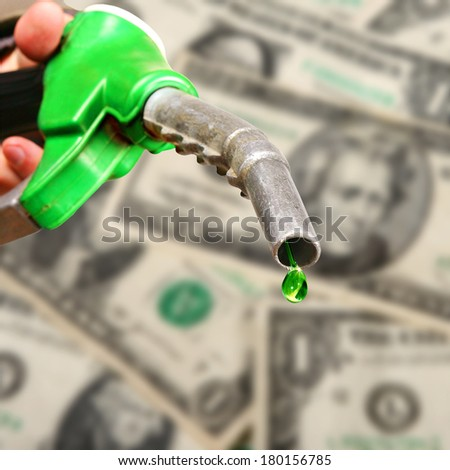 Drop of green fuel on dollar notes background - stock photo