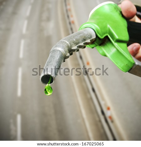 Drop of green fuel on empty road background