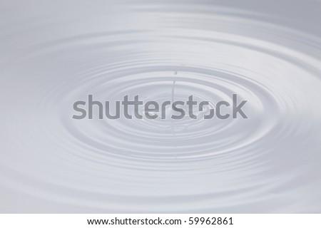 drop of milk splashing and making ripple - stock photo