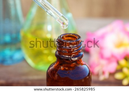 drop of oil dripping from pipette into bottles of essential oil  - stock photo