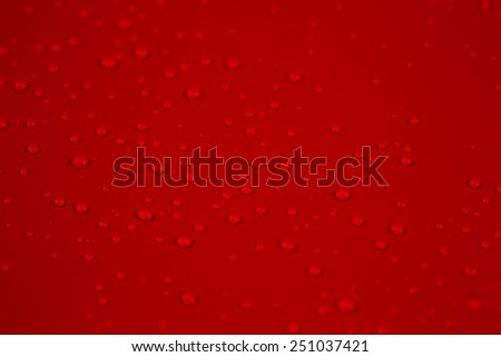 Drop of water on red background  - stock photo