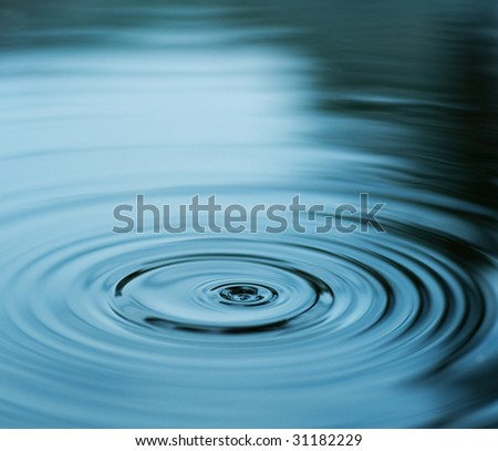 Droplet falling in blue water - stock photo