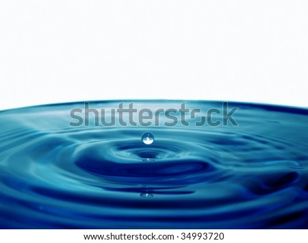 Droplet falling into blue water - stock photo