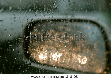 Droplets and car lights reflections through foggy car window and rear view mirror - stock photo