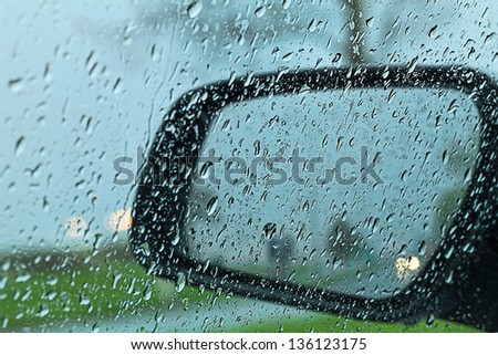 Droplets and car lights reflections through rear view mirror - stock photo