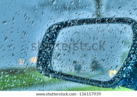 Droplets and car lights reflections through rear view mirror, hdr - stock photo