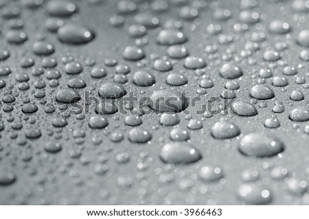 Droplets on a car. Short depth of field. The image may appear grainy, but it's caused by the metallic paint. - stock photo