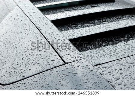 Droplets on black sport car after the rain. - stock photo