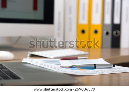 Dropped work. Side view of working place with printed colored charts pens and laptop on foreground cropped big screen and office folders on the background  - stock photo