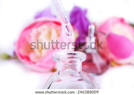 Dropper bottle of perfume with flowers on light background - stock photo