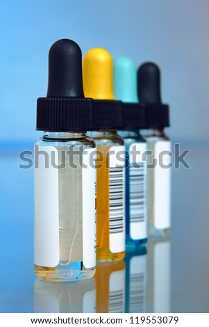 Droppers with reagents in a laboratory workbench - stock photo