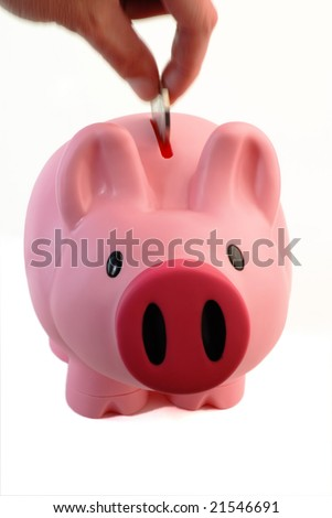 Dropping a coin into a pink piggy bank isolated on white - stock photo