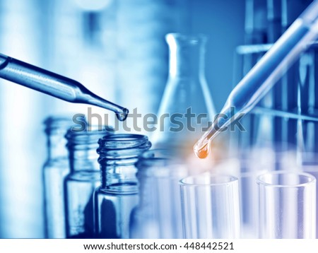 Dropping chemical liquid to test tube, medical and science research concept. - stock photo