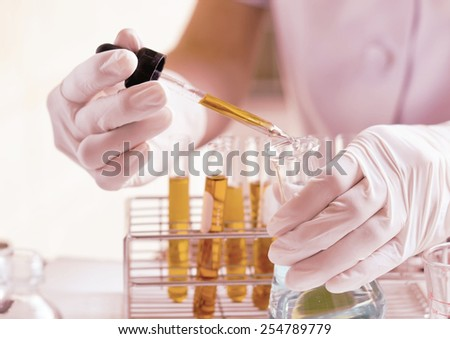 dropping liquid to test tubes - stock photo