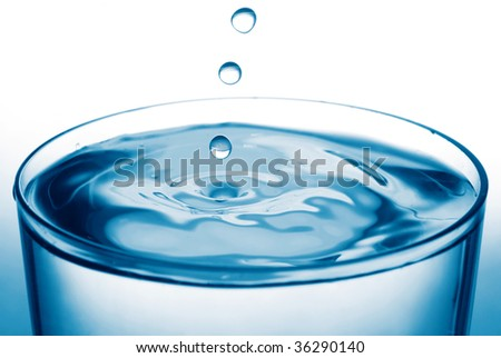 drops falling down into a glass - stock photo