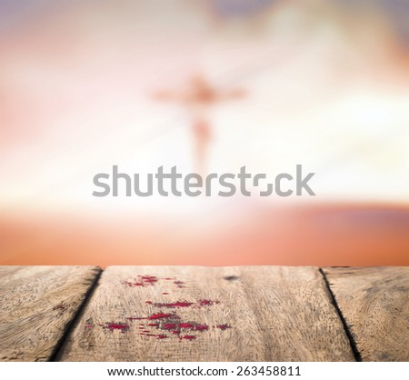 Drops of blood on old wooden floor over blurred Jesus on the cross over a sunset background. - stock photo