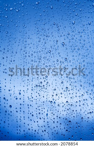 Drops of rain falling on a marquee. Sky and clouds outside. Shallow DOF, centre is sharp, edges variable