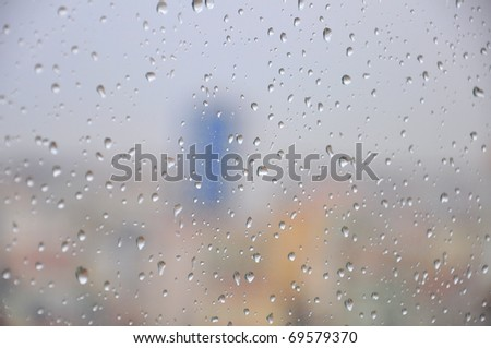 Drops of rain on a window pane, buildings in background - stock photo