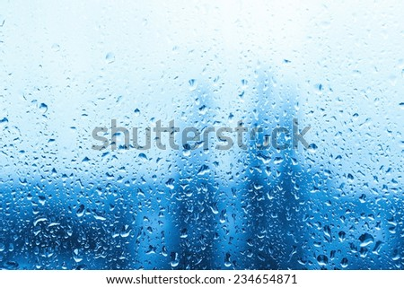 Drops of rain on blue glass background - stock photo