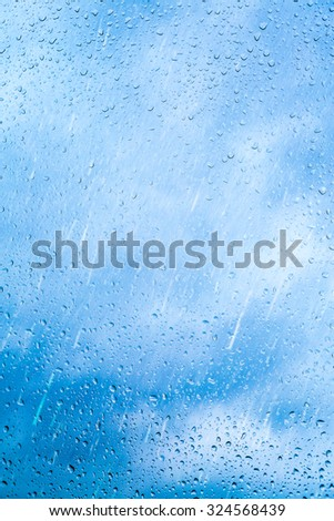 Drops of rain on blue glass background. The sky with clouds on background. - stock photo