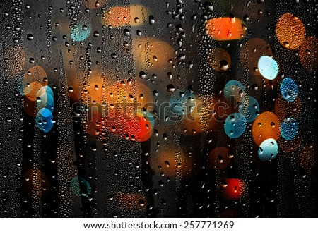 Drops of rain on glass with colorful defocused lights. Abstract background - stock photo