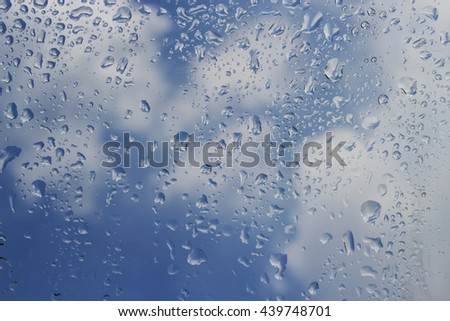 Drops of rain on glass with nimbus background