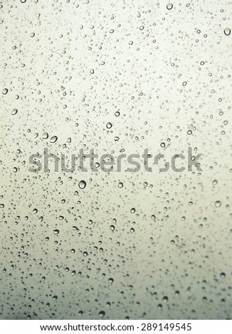 Drops of rain on the inclined window. Shallow DOF - stock photo