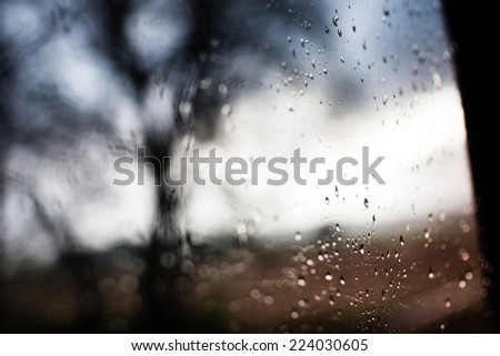 Drops of rain on the train window with tree in background. Dramatic sunrise. Color tone image. - stock photo
