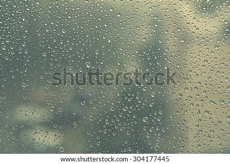 Drops of rain on the window (glass). Shallow DOF. Stylized image - stock photo