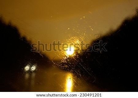 Drops of rain on the windscreen of the car. Sunset. - stock photo
