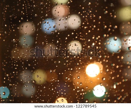 Drops of rain on window, night. On back plan washed away lights of the torches. Shallow DOF - stock photo