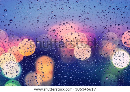 Drops of rain on window with abstract bokeh background - stock photo