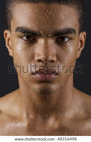 Drops of the water on face of a young man on black background. - stock photo